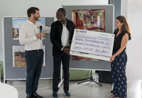 Mathias (left) and Sarah Hevert symbolically handing over the check to Diébédo Francis Kéré in Berlin.